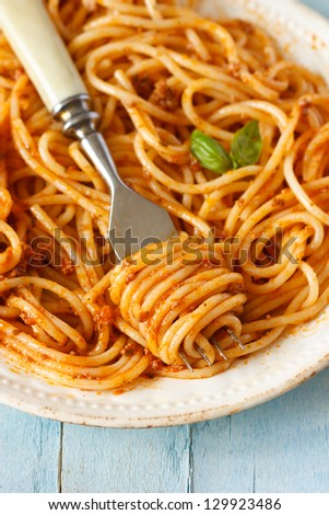 Spaghetti bolognese with fork in an old rustic plate close-up.