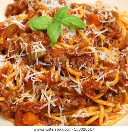 Spaghetti bolognese with grated Parmesan cheese.