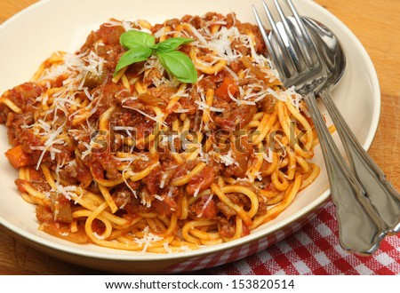 Spaghetti bolognese with shredded Parmesan cheese.