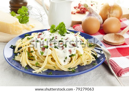 spaghetti carbonara meal surrounded by ingredients and kitchen utensils