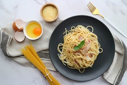 Spaghetti Carbonara  (Pasta Alla Carbonara) and some ingredients on white marble background -Top view