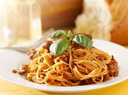 spaghetti dinner with basil garnish in meat sauce