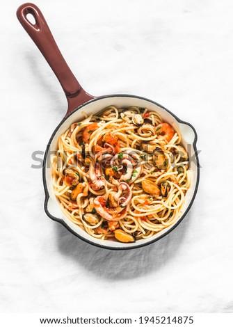Spaghetti frutti di mare in cooking pan on a light background, top view. Delicious traditional mediterranean food         Foto d'archivio ©
