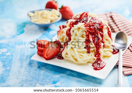Spaghetti ice cream dessert with strawberry fruit topping in close up view