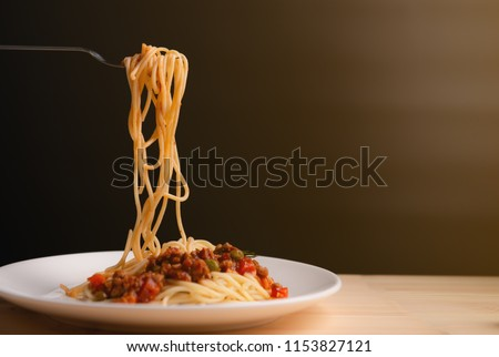 Spaghetti in tomato sauce with pork on fork on black background,Delicious spaghetti in tomato sauce with bacon served on plate,Parsley in dish,Spaghetti pasta with copy space,Italian food,