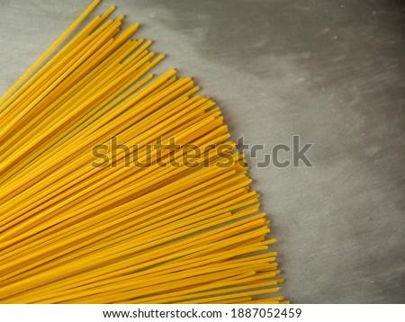 Spaghetti lunghi gialli su fondo grigio. Pasta sottile disposta in file. Pasta italiana gialla. Spaghetti lunghi. Carta da parati spaghetti crudi. Spaghetti sottili. Concetto di sfondo alimentare. Foto stock ©