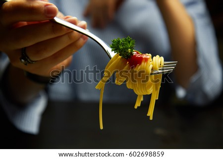 Spaghetti on a fork. Girl keeping fork with spaghetti. Pasta with red sauce and parsley.