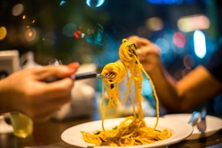 Spaghetti on a fork. Hand of two woman rolling spaghetti and keeping on a fork for eat. Beautiful colorful and light bokeh at night in the background.