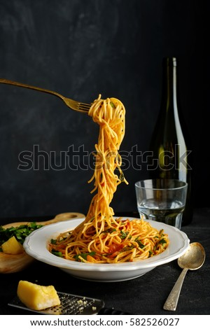 Spaghetti on a fork. Pasta with fresh tomatoes and herbs
