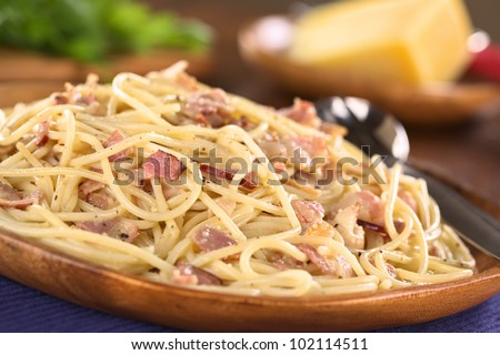 Spaghetti (Pasta) alla Carbonara with bacon, cheese, egg, cream on rustic wooden plate with parmesan cheese in the back (Selective Focus, Focus one third into the meal)