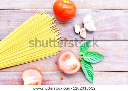 Spaghetti pasta angle hair uncooked with tomatoes, garlic and basil top view, flat lay on wooden board background, space for copy right side of picture, ingredients Italian food preparation concept