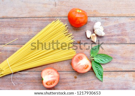 Spaghetti pasta angle hair uncooked with tomatoes, garlic and basil top view, on wooden board background, space for copy right side of picture, ingredients Italian traditional preparation food concept