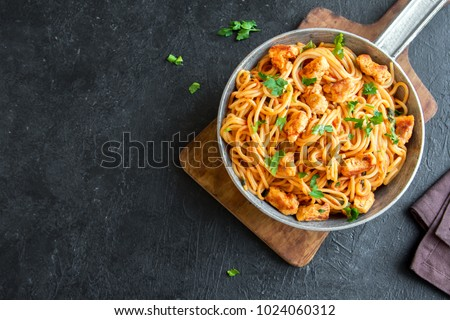 Spaghetti pasta in tomato sauce with chicken,  parsley in pan. Chicken spaghetti pasta over black stone background with copy space, italian food.