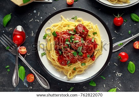 Spaghetti pasta meatballs with tomato sauce, basil, herbs parmesan cheese on dark background