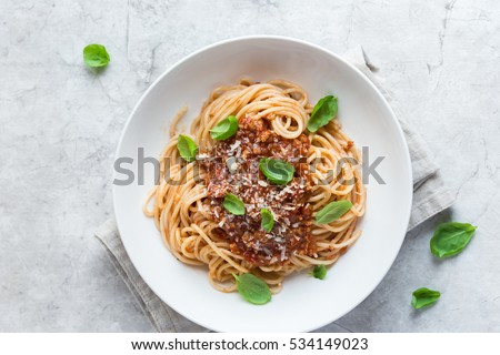 Spaghetti pasta with bolognese sauce and  parmesan cheese, top view.
