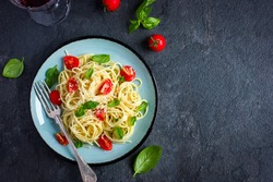 Spaghetti pasta  with cherry tomatoes,  basil and parmesan cheese, top view, copy space