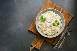 Spaghetti pasta with creamy mushroom sauce on a on wooden cutting board, gray rustic background. Italian traditional dish. Top view, copy space