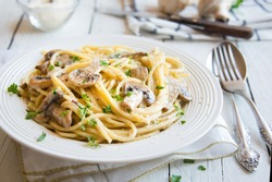 Spaghetti pasta with mushrooms, creamy sauce and parsley on white background