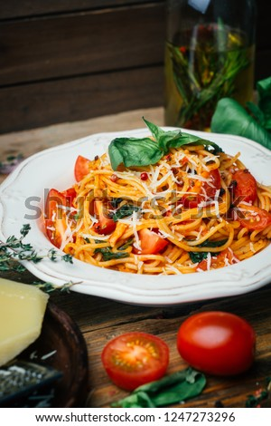 Spaghetti pasta with tomato sauce, parmesan and basil on a white plate. The classic tomato spaghetti: vegetarian tomato basil pasta. Old wooden background