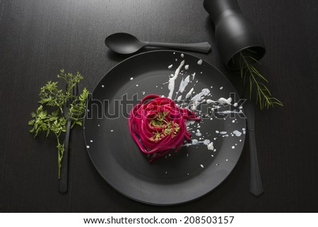Spaghetti roses, black place setting, pasta dyed with food coloring on rustic wooden table black #208503157