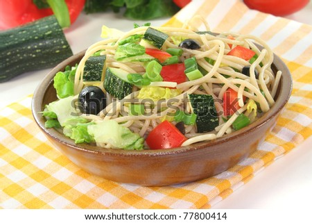 Spaghetti salad with lettuce, peppers, zucchini, olives, and green onions on a white background
