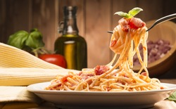 spaghetti with amatriciana sauce in the dish on the wooden table