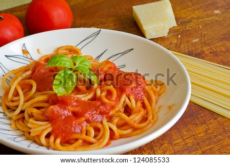 spaghetti with basil and sauce un a ceramic plate - stock photo