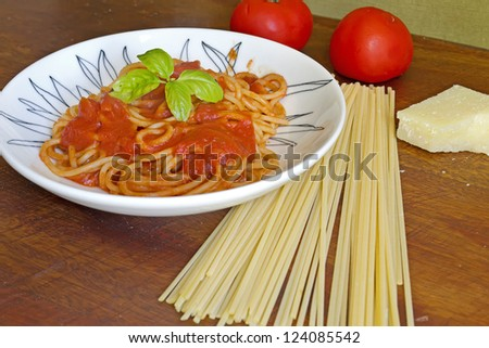 spaghetti with basil and sauce un a ceramic plate