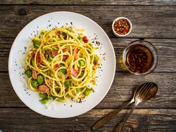 Spaghetti with broad bean, bacon and parmesan on wooden table