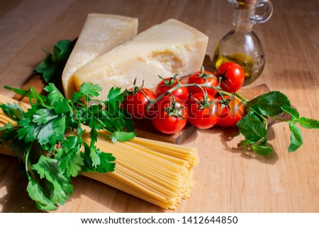 spaghetti with cheese, cherry tomatoes and mint. ingredients for pasta. spaghetti on wooden background. copy space