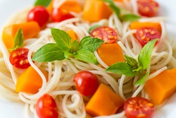 spaghetti with chunks of pumpkin and tomatoes