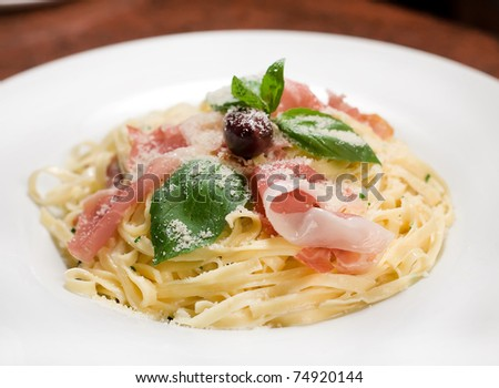 Spaghetti with cream decorated with prosciutto. basil and olive
