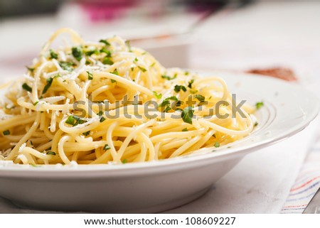 Spaghetti with fresh basil leaves on white dish