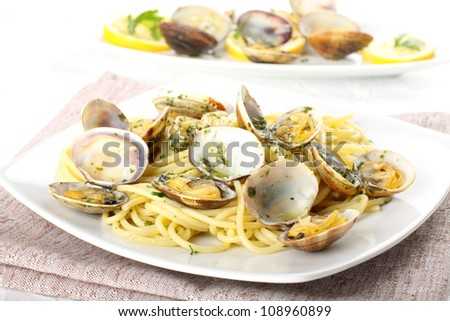 Spaghetti with fresh clams, garlic and parsley on complex background