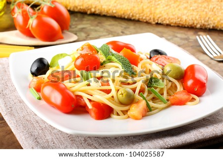 Spaghetti with fresh tomatoes, olives and mint on complex background