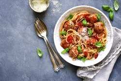 Spaghetti with meatballs in tomato sauce in a white craft bowl on a grey slate,stone or concrete background.Top view.