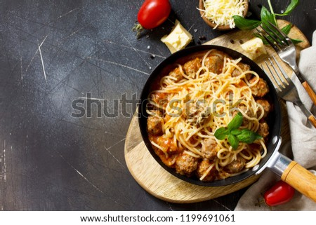 Spaghetti with Meatballs with Tomato Sauce and Parmesan Cheese on a dark stone or concrete background. Top view flat lay background. Copy space. #1199691061