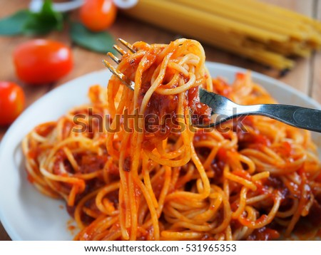 Spaghetti with minced beef tomato sauce and fresh basil on wooden table.