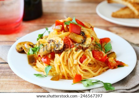 Spaghetti with mushrooms and peppers on a white plate, food #246567397