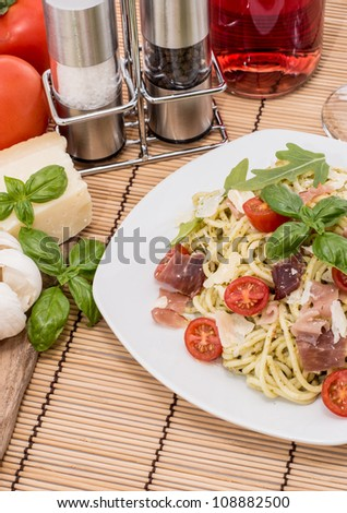Spaghetti with Pesto Sauce and ingredients in the background