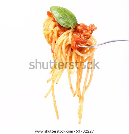 Spaghetti with sauce bolognese hanging on a fork decorated with fresh basil