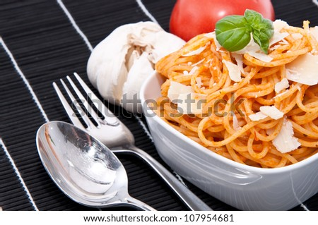 Spaghetti with sauce ingredients on a black tablecloth