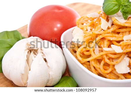 Spaghetti with sauce ingredients on a cutting board