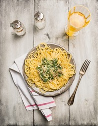Spaghetti with spinach and minced meat, glass of wine and fork on rustic wooden background, top view