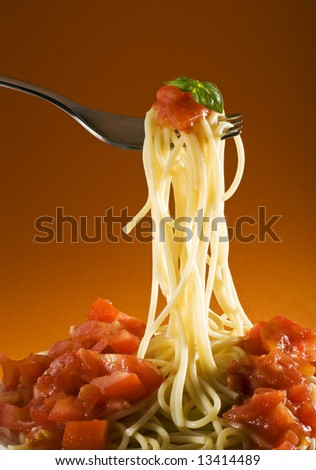 spaghetti with tomato and basil on fork close up