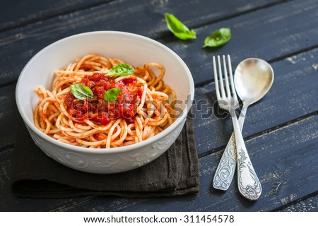 spaghetti with tomato sauce and Basil in a white bowl on a dark wooden surface