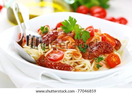 stock photo : Spaghetti with tomato sauce, sun dried tomato and shrimps on white plate