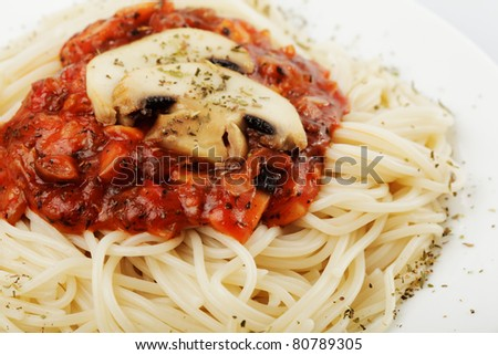 Spaghetti with tomato souce and champignons on white plate