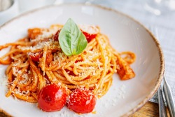 Spaghetti with tomatoes in a plate on the table. Traditional Italian cusine. Close-up.