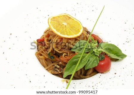 Spaghetti with vegetables decorated with greenery on a white background